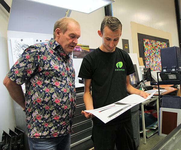Mensen bekijken drukwerk op de werkplaats