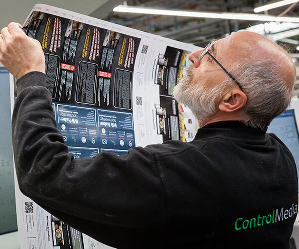 Man controleert de kwaliteit van drukwerk